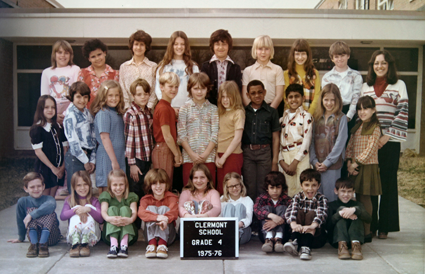 Fourth grade class photograph taken during the 1975 to 1976 school year. 28 children and their teacher are pictured. They are posing on the sidewalk in front of the main entrance to the school.
