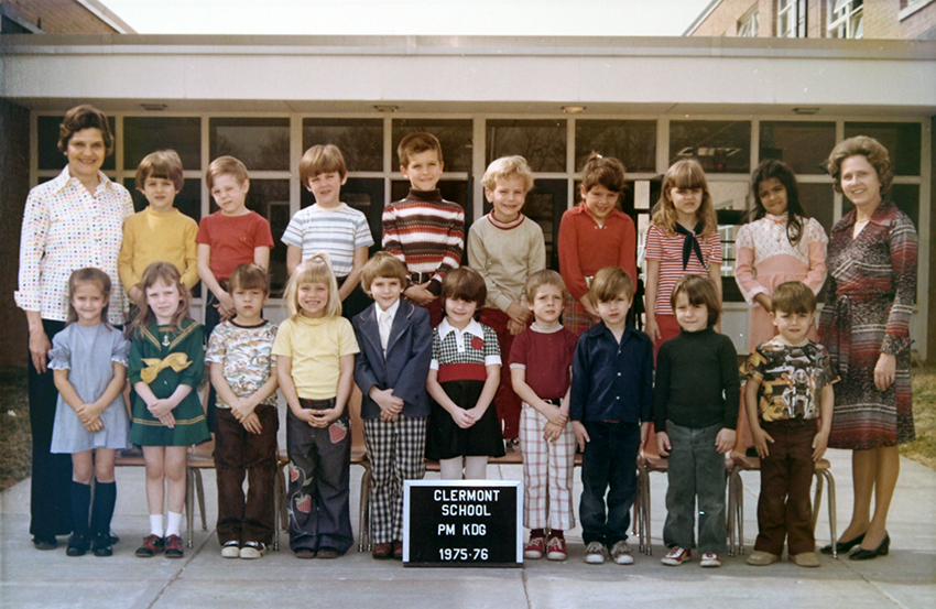 Afternoon kindergarten class photograph taken during the 1975 to 1976 school year. 18 children and two teachers are pictured. They are posing on the sidewalk in front of the main entrance to the school.