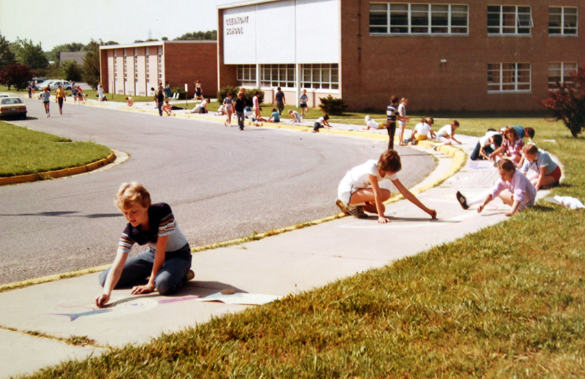 Color photograph of the front exterior of Clermont Elementary School taken in 1981. Several students are sitting on the sidewalk in front of the school coloring the sidewalk with chalk.